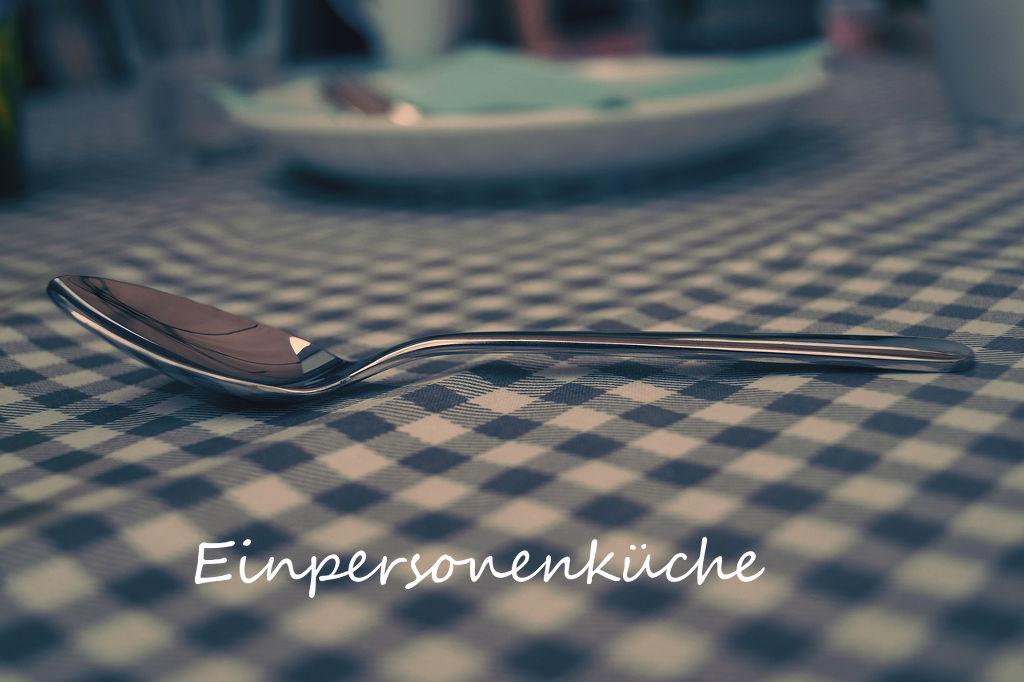 Eßlöffel auf Tischtuch, Schriftzug Einpersonenküche